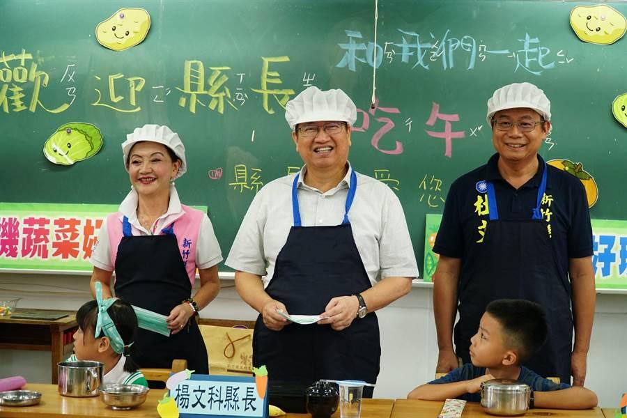 新竹縣長楊文科(圖中)換上廚房衣帽,充當打菜大叔,並與學生一起共享用在地有機蔬菜午餐。(台灣閱讀文化基金會提供)