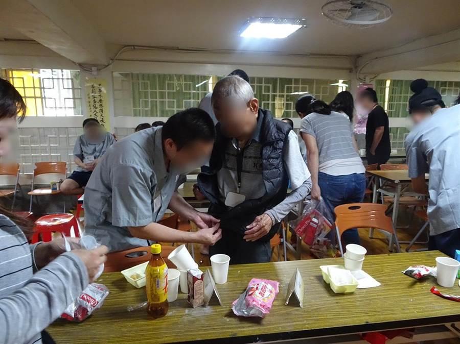 台北看守所4日在所內舉辦面對面懇親活動,開放百位收容人在佳節前夕與父母妻小面對面相聚;收容人細心為久未見面的家人繫上拉鍊。(許哲瑗攝)