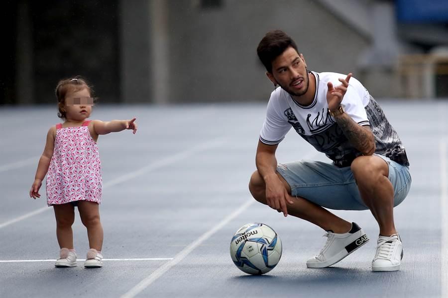 殷亞吉有傷在身,今天練球只能穿著便服,在場邊與女兒玩球。(李弘斌攝)