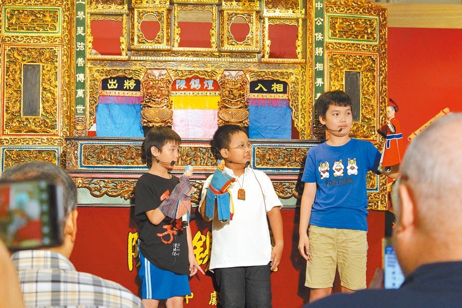 國寶級布袋戲大師陳錫煌,致力傳承傳統文化,連國小生都是戲迷,跟著學習操偶技術。(王寶兒攝)