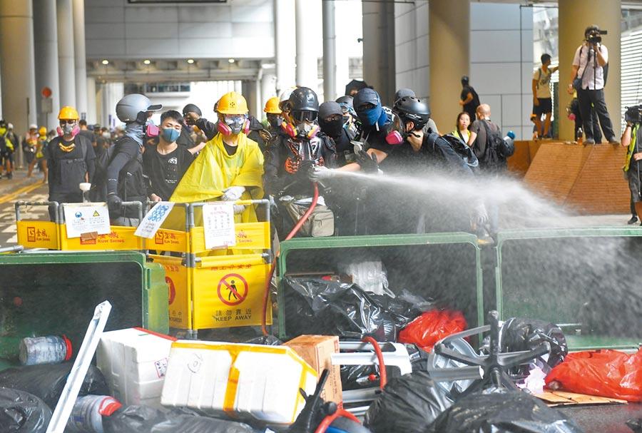 香港特首林鄭月娥憂心「大規模破壞活動」重創香港。圖為9月1日,激進示威者聚集香港機場破壞設施,向警員投擲雜物。(新華社)
