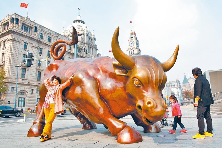 遊客在上海外灘金融廣場與金融牛合影。(中新社)