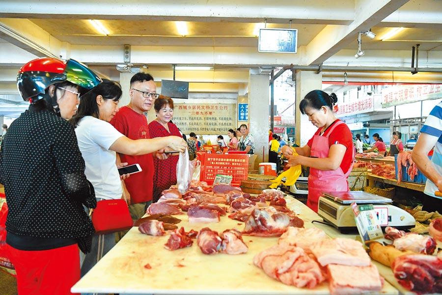 9月3日,廣西南寧市麻村市場內,市民正在選購豬肉。(中新社)