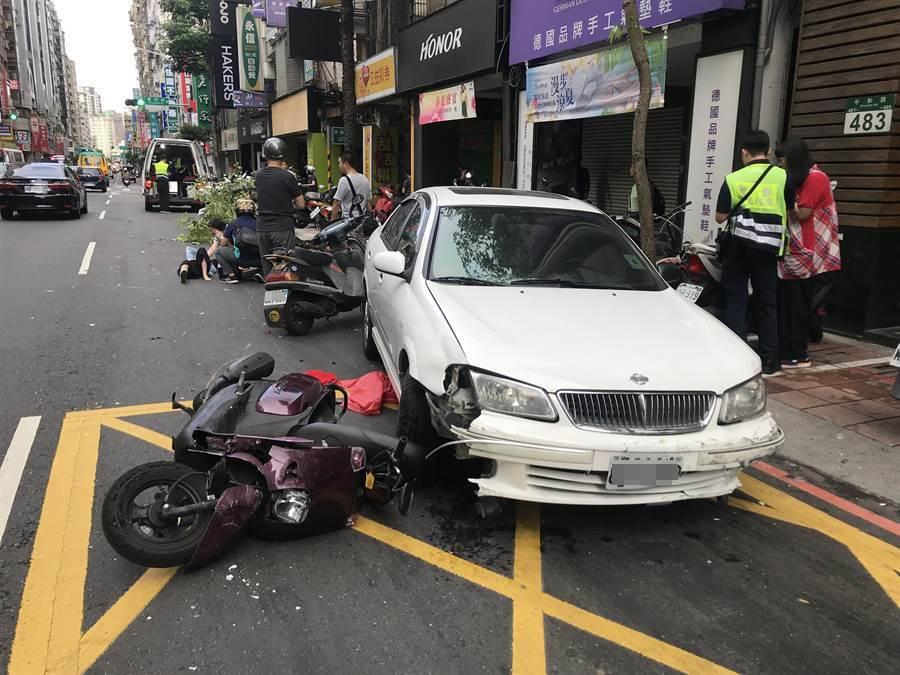 白色轎車疑似逆向衝撞對向車道,撞擊路邊停放的10多部機車,並將路樹撞倒連根撞斷。(陳信翰攝)