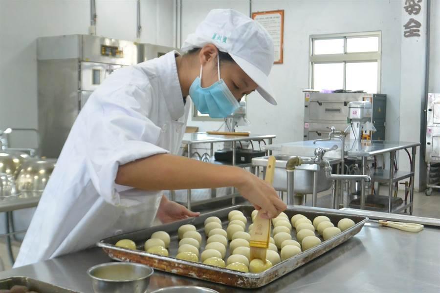 捏製好的月餅刷上蛋黃,圓滾滾的月餅將送入烤箱,香氣撲鼻。(巫靜婷攝)