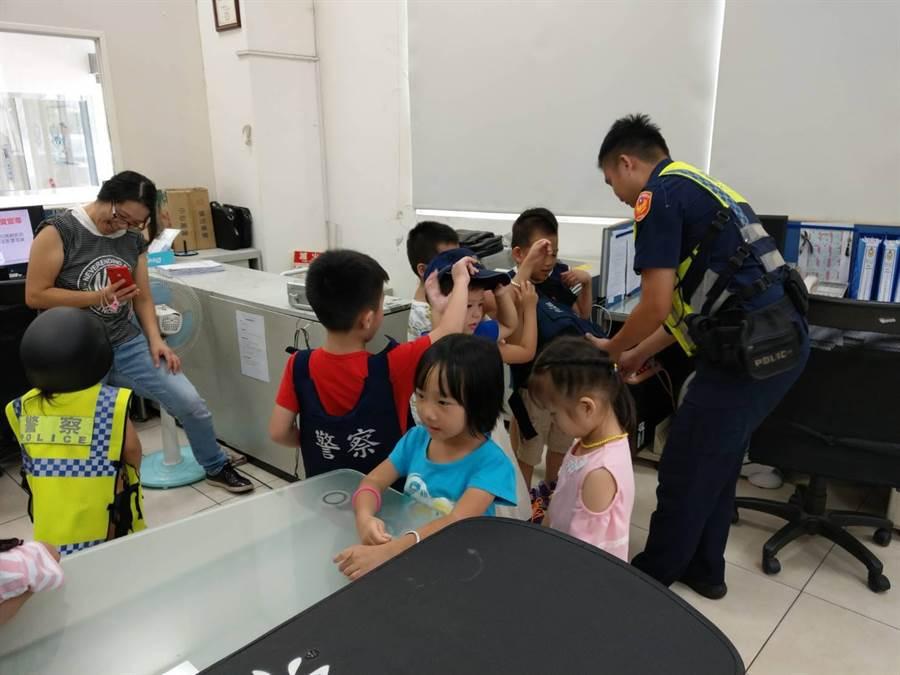 60名孩童到龍潭派出所參訪,還試穿反光背心與防彈背心。(龍潭分局提供/邱立雅桃園傳真)