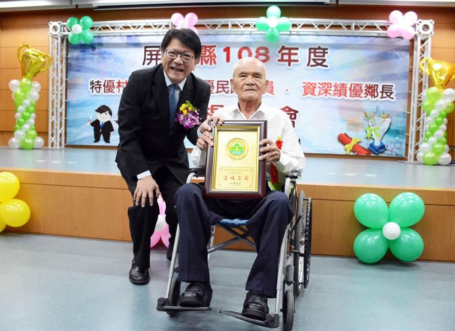 80歲鄰長楊善道從屏東縣長潘孟安手上接獲獎牌,行動不便的他仍對這分無給職工作充滿熱忱。(林和生攝)