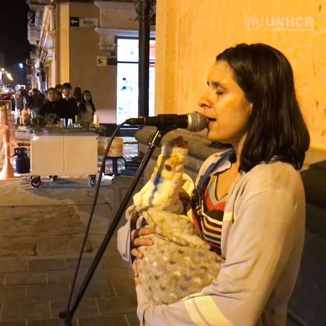 這名母親是來自委內瑞拉(Venezuelan)的難民,每天她都會站在祕魯(Peru)的街頭2小時賣唱。在短短40秒的影片中能看見這位媽媽不停地安撫著懷中的寶寶,影片的尾端她輕輕地親吻了孩子的額頭。(圖/取自聯合國難民署影片)