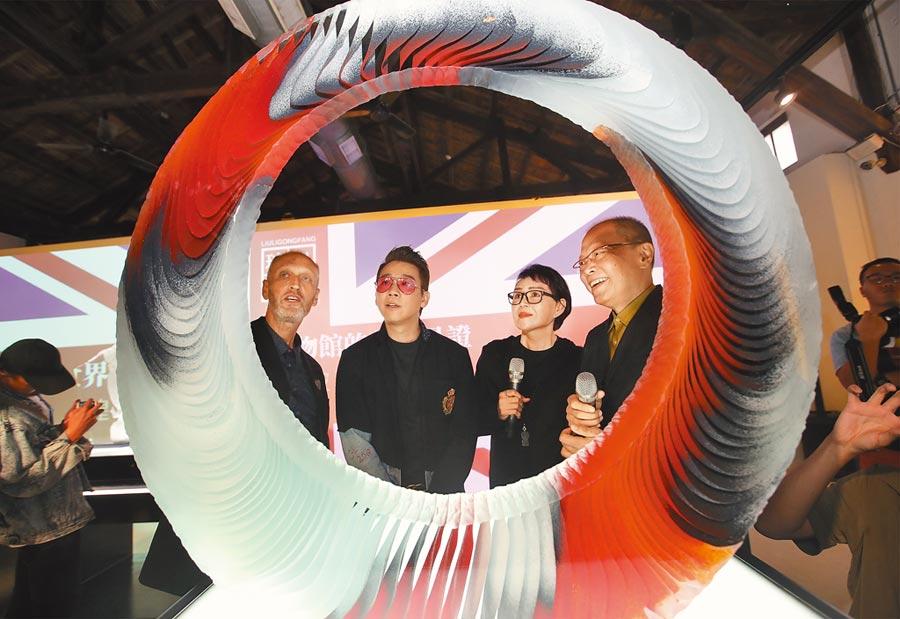 琉璃工房主辦《一縷光芒的奇蹟》英國窯鑄玻璃藝術展,創辦人張毅(右起)、楊惠姍與藝人陶喆在英國策展人柯林‧雷德的介紹下,欣賞他的作品《風火之環》。(鄭任南攝)
