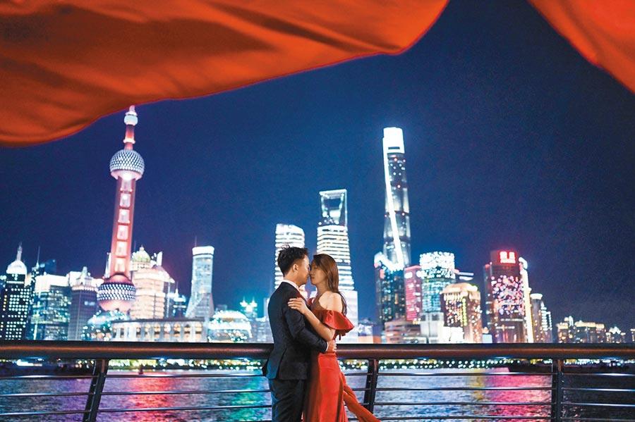 上海是國際大城,吸引許多年輕人,圖為一對青年男女在上海外灘拍攝婚紗照。(新華社資料照片)
