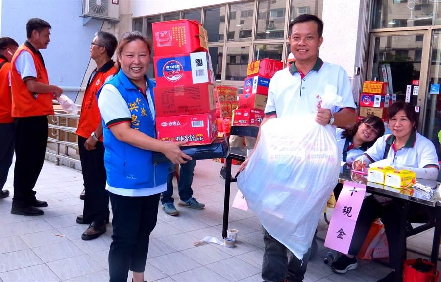 埔里鎮民代表洪惠梅見低收入提不動發放的物品,不忘協助幫忙搬運。(楊樹煌攝)