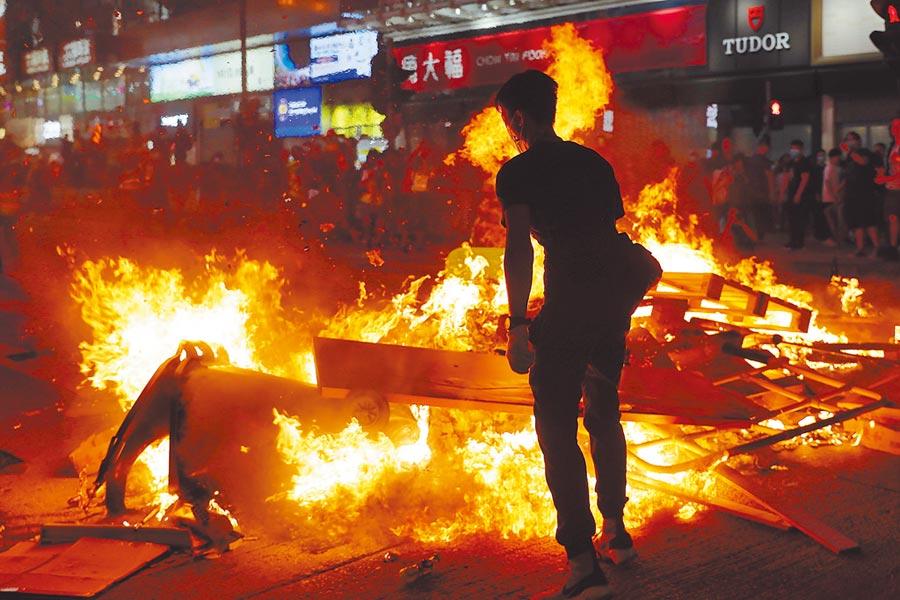 信評機構惠譽6日調降香港信貸評級,就在當天,示威民眾和警方再次爆發衝突。圖為香港旺角,示威者在街頭放火,熊熊大火令人觸目驚心。(美聯社)