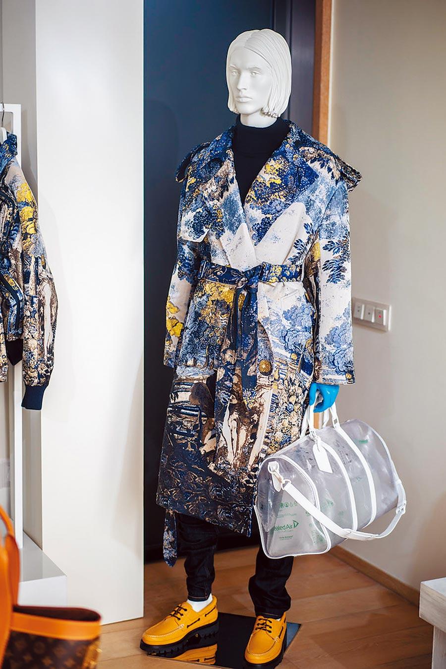 以拉菲爾拼貼畫作為緹花的風衣外套做工精細,搭配透明粒面手袋,讓度假也能優雅奢華。(LV提供)