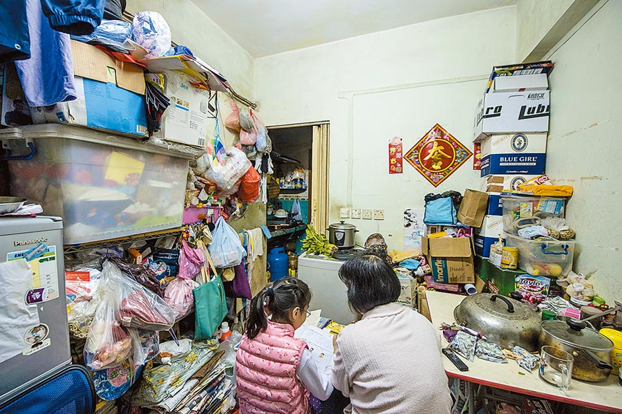 2016年1月19日,香港荔枝角道一處17平方米的房間內,母親為女兒溫習功課。這間斗室每月租金約4000港元。(新華社)