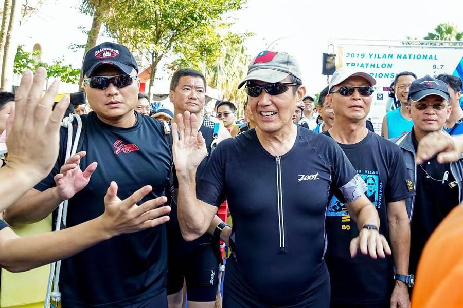 前總統馬英九昨赴宜蘭梅花湖參加鐵人三項半程賽,抵達比賽會場後他與選手們擊掌勉勵。(李忠一攝)