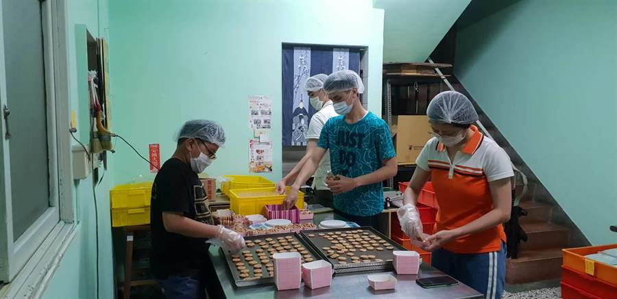 新永安有線電視志工隊扮演「1日志工」伸出溫暖的手,包著一顆一顆蛋黃酥和一片片手工餅乾,協助身心障礙青年們做出更多好吃月餅,秋節前爭取更多訂單!(曹婷婷攝)