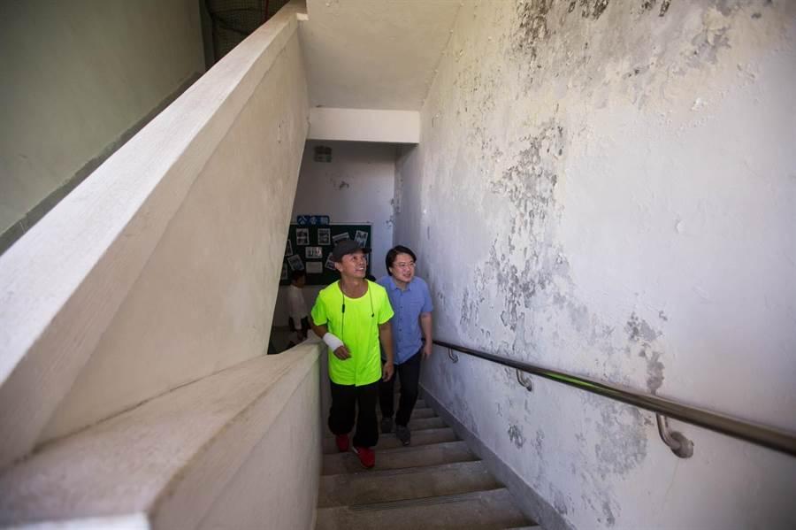基隆市仁義里民活動中心漏水問題嚴重,市長林右昌(右)接獲仁義里長王柏力(左)反映後,前往會勘牆面的壁癌。(基隆市政府提供)