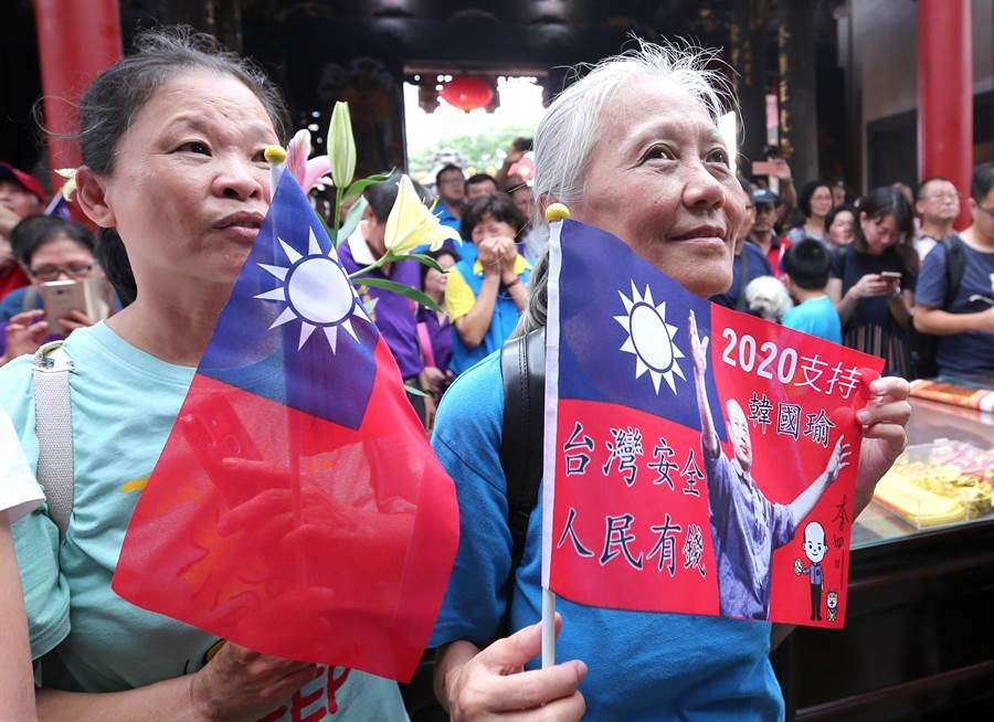 支持者拿著國旗與挺韓旗幟,專注聆聽韓國瑜講話。(黃世麒攝)