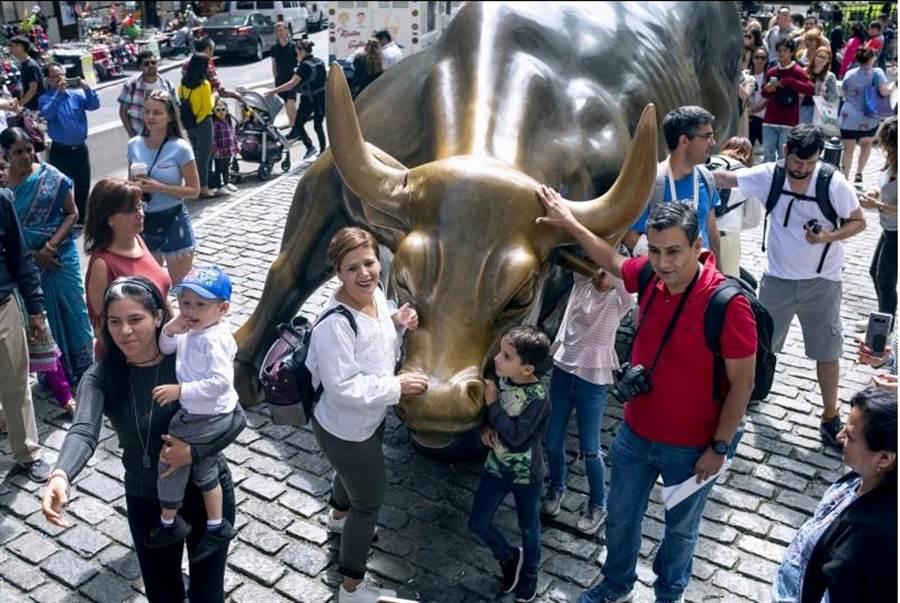 遊客聚集在紐約著名的華爾街銅牛旁照相。(美聯社)