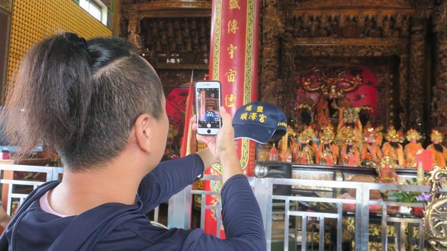 住在隔壁村的居民游先生專程跑來廟裡詢問能否索取帽子,並借廟方人員的帽子拍照打卡。(謝瓊雲攝)