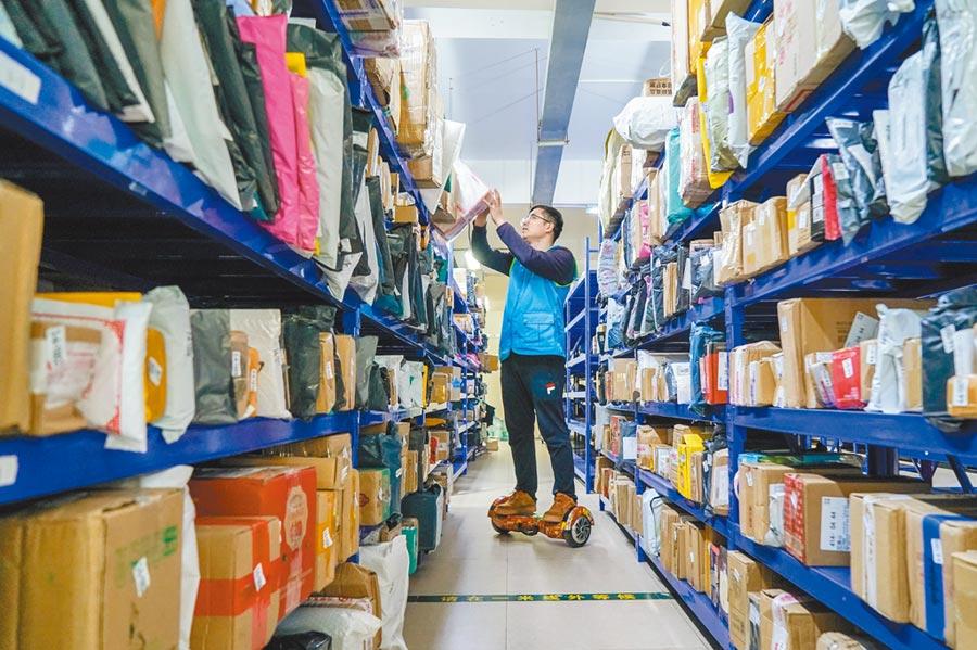 江蘇昆山市的物流公司內,工作人員整理網購包裹。(新華社資料照片)