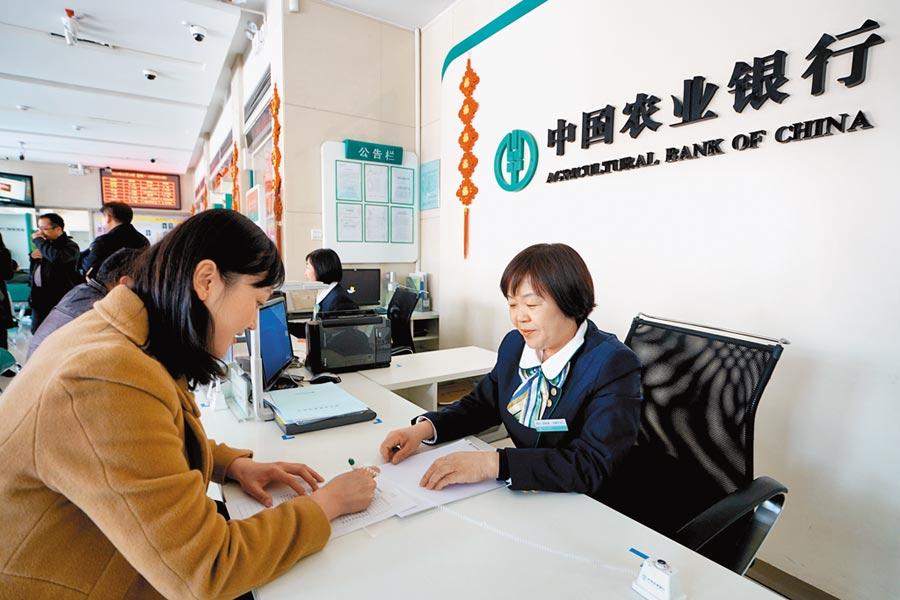 中國農業銀行工作人員為顧客辦理業務。(新華社資料照片)