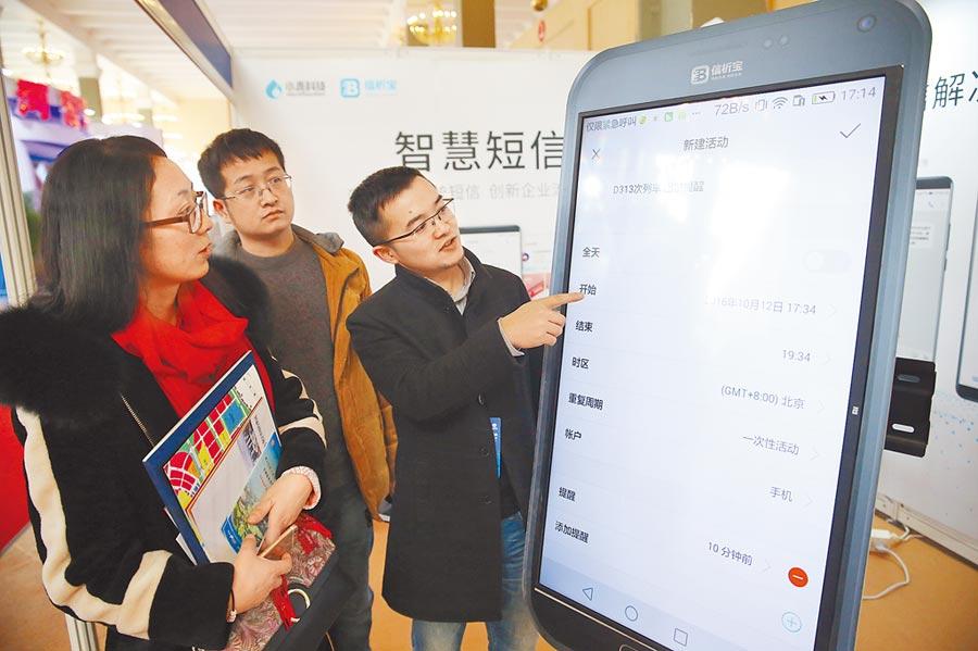 2018年1月25日,工作人員在北京國際金融博覽會介紹涵蓋理財查詢、保險產品、企業訊息等功能的「智慧短信」。(新華社)