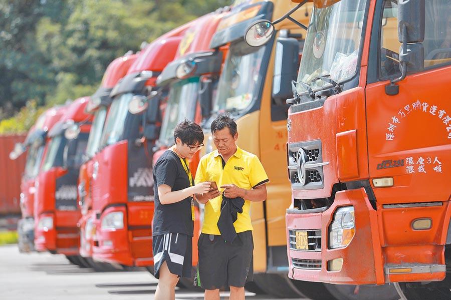 8月1日,工作人員幫助貨車司機使用貨車幫APP。(新華社)