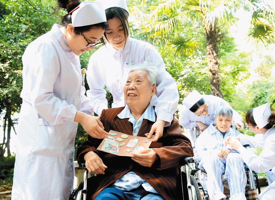 大陸老年醫療照護缺口龐大。圖為2016年5月11日,上海滬東老年護理院的護士為老人製成心願卡。 (新華社)