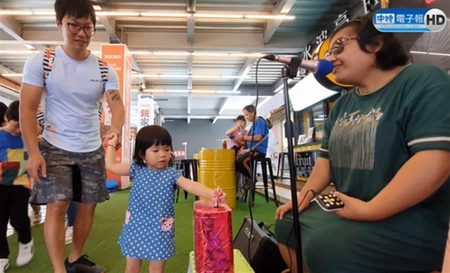 年輕爸爸支持弱勢,實際行動帶小孩一同做投錢作愛心。(照片/游定剛 拍攝)