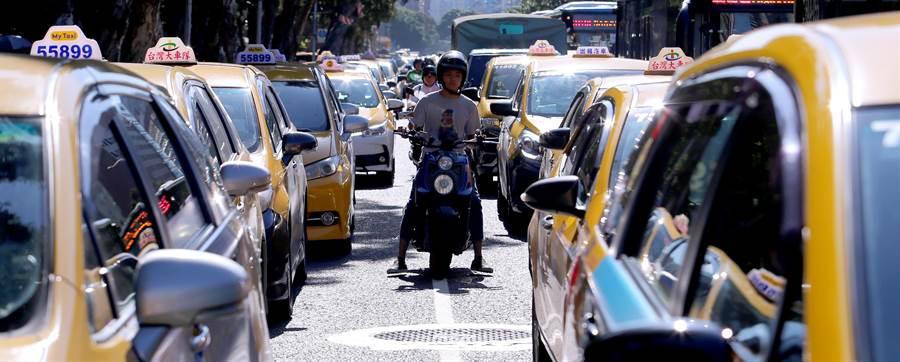 上班尖峰時段的台北市忠孝東西路、中山南北路大塞車,機車騎士只能鑽車縫趕上班。(黃世麒攝)