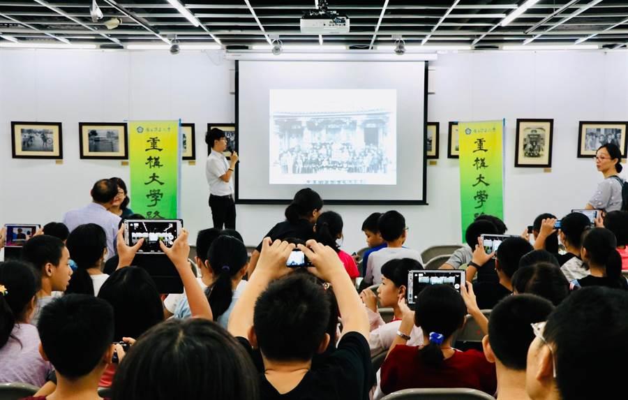 七星藥局藥師吳至鎧精選20張展覽照片介紹,台下學生聽得津津有味,並拿起數位相機拍照。(張亦惠攝)