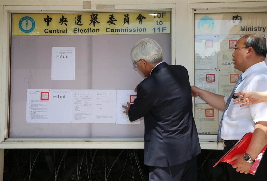 中選會12日張貼第15屆總統副總統選舉公告,中選會主委李進勇(左)一開始貼錯地方,經提醒才貼在正確的位置。(陳君瑋攝)