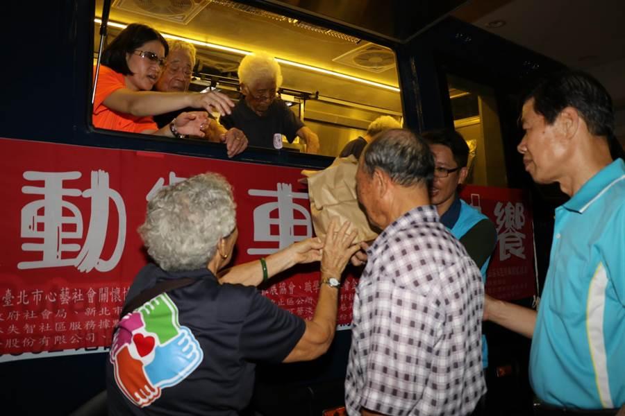91歲的貢寮阿嬤吳王月(車上右2)在行動餐車上調理九孔鮑油飯,分送給其他據點長輩享用。(社會局提供/葉書宏新北傳真)