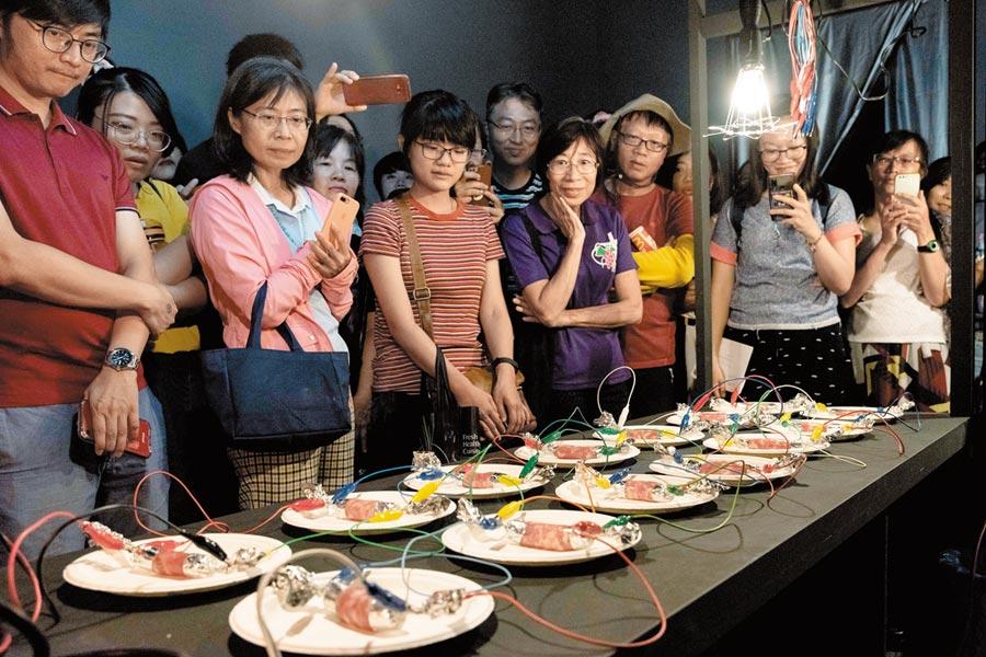 藝術家木村崇人以電線烤熟香腸,做為高雄駁二「不正經調查局」開幕表演。  (林宏聰攝)