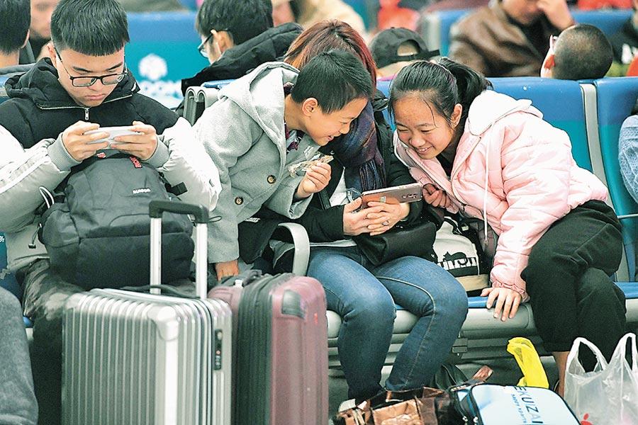 福州火車站內,兩名小孩圍在媽媽旁邊看片。(中新社資料照片)