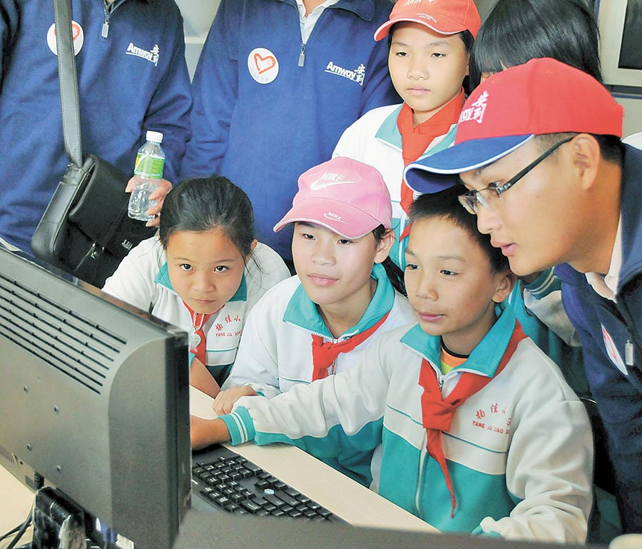 志工在海南某一小學內教孩子們使用電腦。(新華社資料照片)