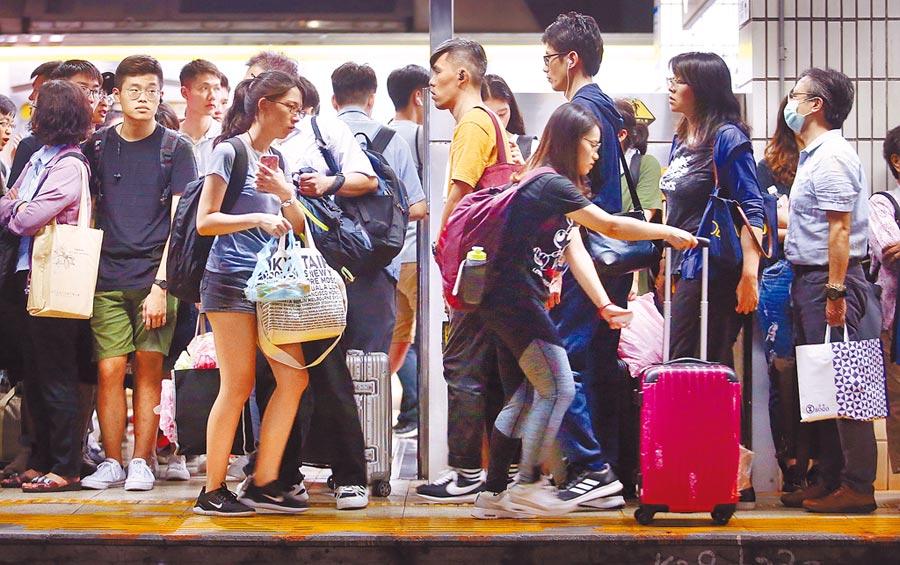中秋連假開始,許多民眾12日傍晚起前往台北車站搭車返鄉,月台上擠滿候車旅客。(范揚光攝)
