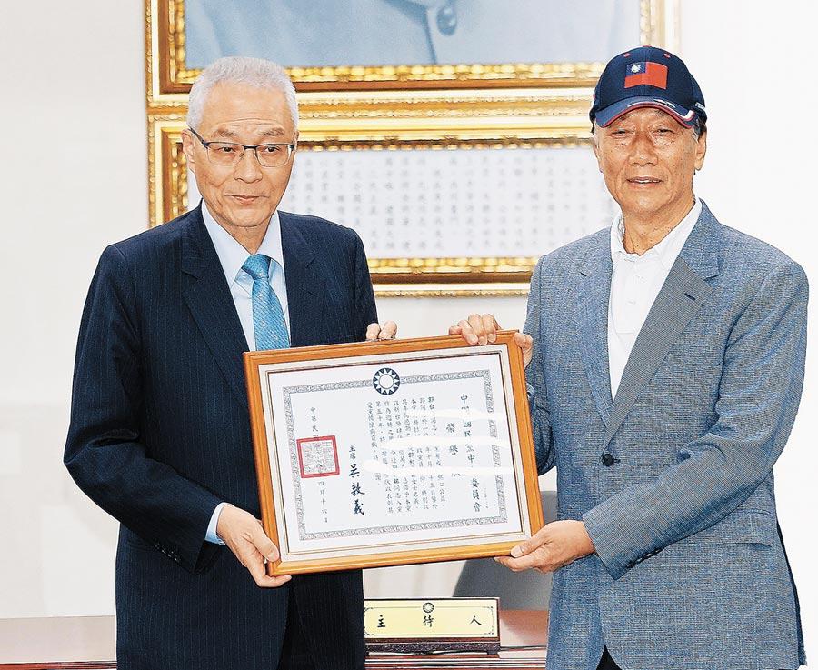 鴻海創辦人郭台銘(右)4月17日從國民黨主席吳敦義(左)手中接下榮譽狀。(本報系資料照片)
