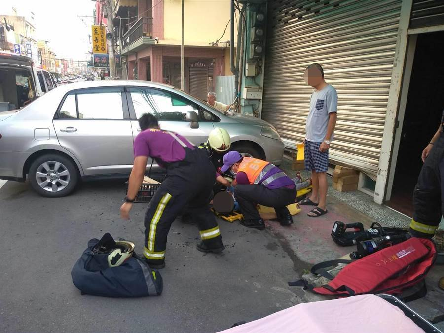 婦人卡於鐵捲門下,警消緊急將人搶救送醫不治。(桃園市消防局提供/呂筱蟬桃園傳真)