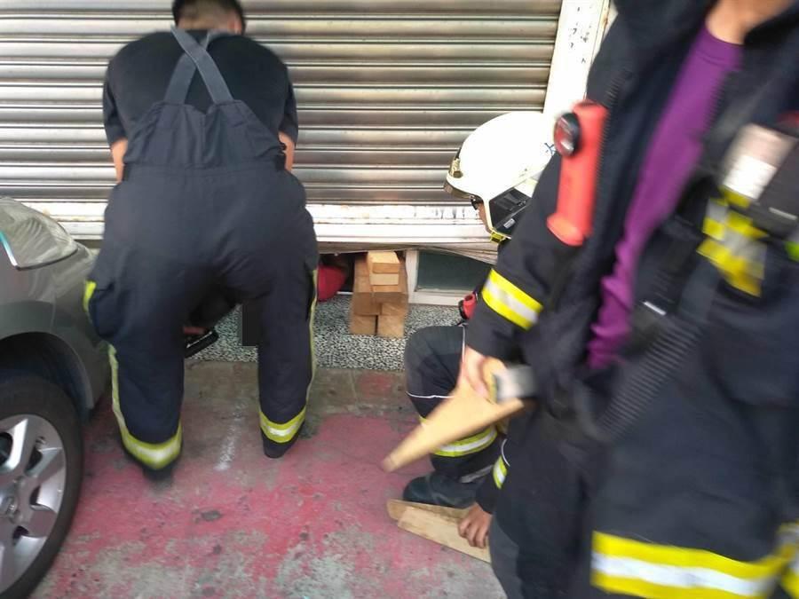 警消搶救卡在鐵捲門下的婦人。(桃園市消防局提供/呂筱蟬桃園傳真)