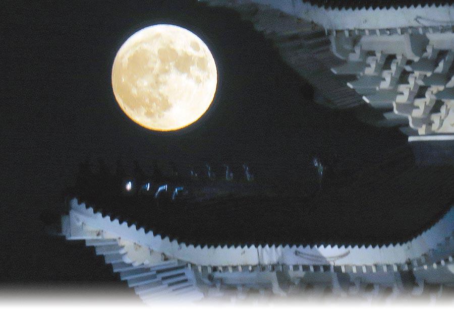 中秋節到來,13日晚間月亮緩緩升起,高掛中正紀念堂簷角。而今晚的月亮才是真正的滿月,天文館強調今年農曆8月的滿月,是26年來最小滿月。