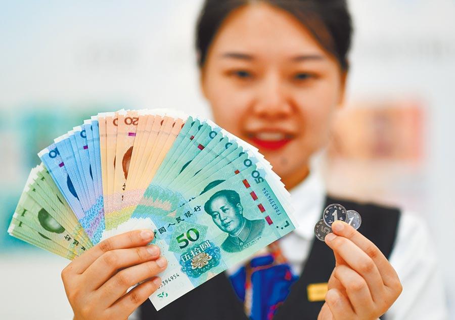 中國工商銀行北京復興門支行員工展示2019年版第五套人民幣。(新華社資料照片)