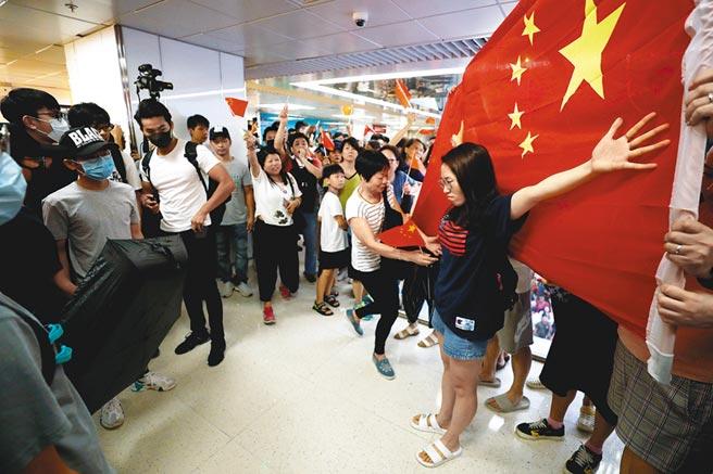 香港一名女子張開雙手擋在五星旗前,與反送中民眾對峙。(路透)