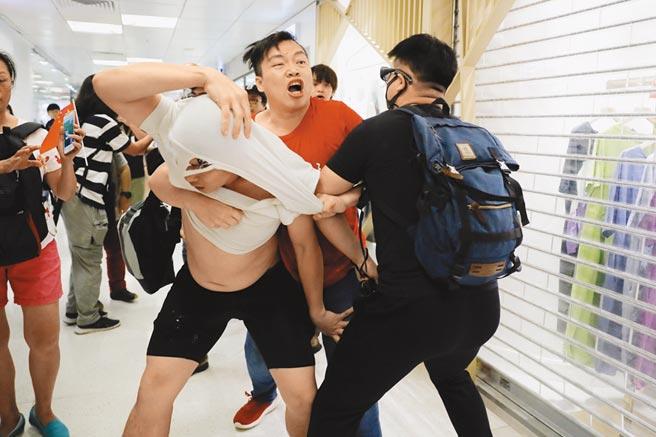 「反送中」議題意見相左的兩派香港市民,14日在九龍灣淘大商場內爆發肢體衝突,穿紅衣的男子使出鎖喉術,勒住反對修例民眾的脖子,甚至把對方的衣服差點都撕爛了。(美聯社)
