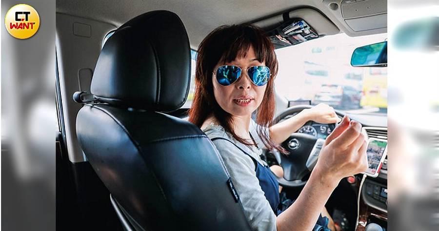 愛美的菲菲戴上墨鏡、熟練的打著方向盤,讓乘客一上車就感覺得到司機是個穩當的駕駛。(圖/馬景平攝)