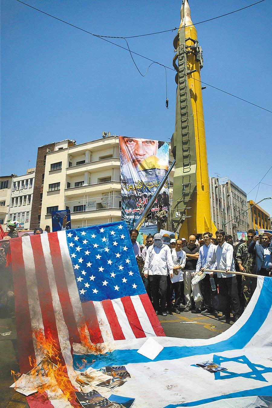 德黑蘭舉行反美、反以色列集會,群眾焚燒美、以國旗,背後矗立著彈道飛彈。美在中東的基地和航母都在射程內,伊朗揚言已做好全面戰爭的準備。(美聯社)