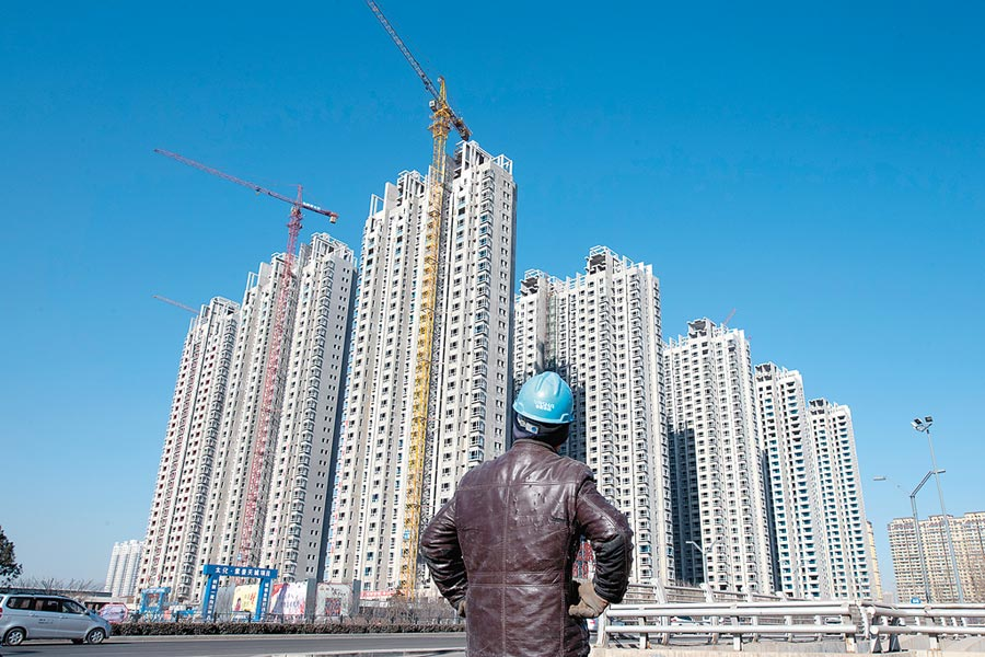山西太原,建築工人經過一處正在建設中的房地產項目。(中新社資料照片)