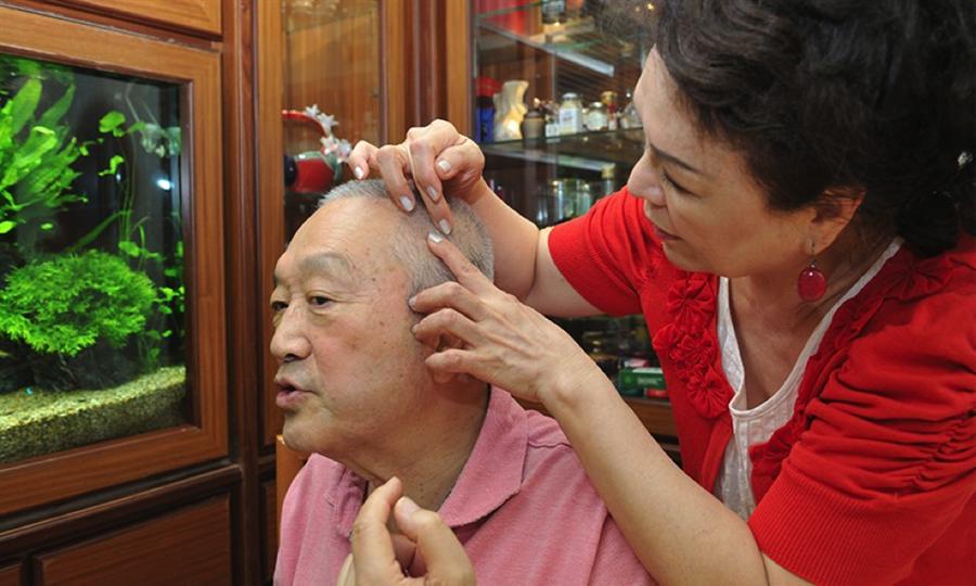 侯麗芳指著老公頭上因為脂肪瘤動刀的疤痕,感謝醫生細心將刀痕藏在髮際線裡。(圖片來源:陳德信攝)
