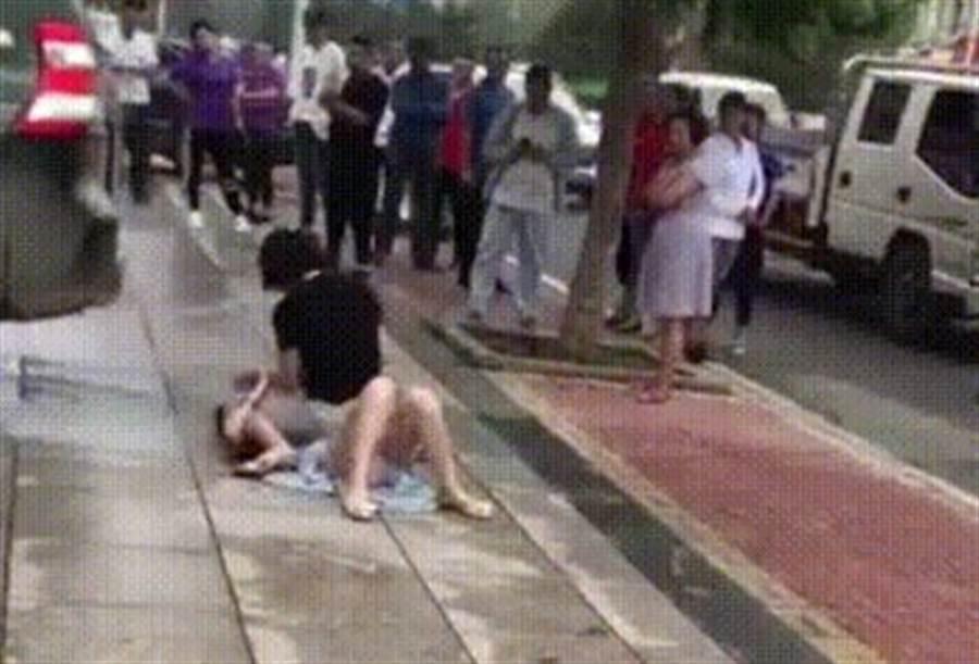 小三街上遭正宮壓倒在地狂毆,卻無人上前勸阻。(圖/翻攝自微博)